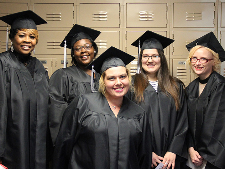 group of graduates smiling in the hallway
