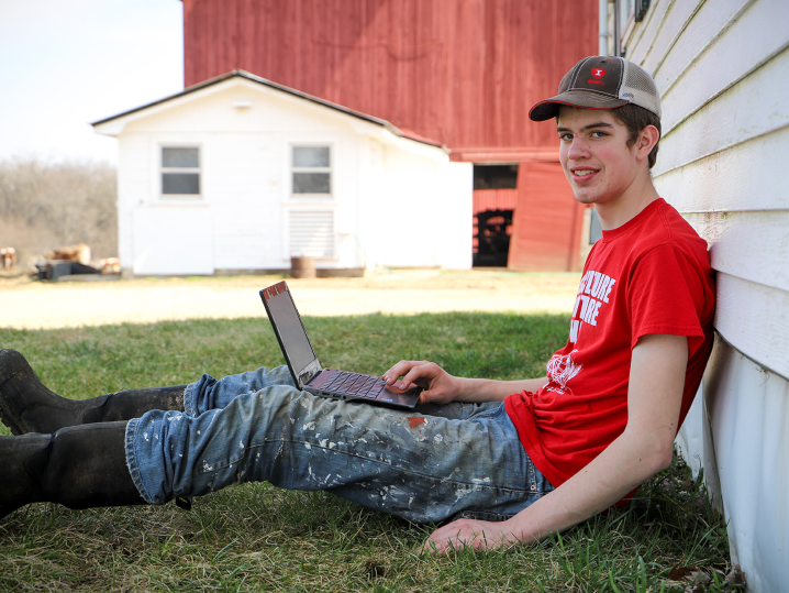 male student sitting outside using laptop