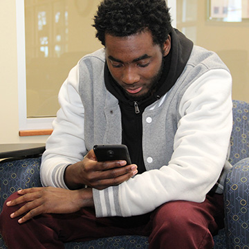 student sitting down using phone